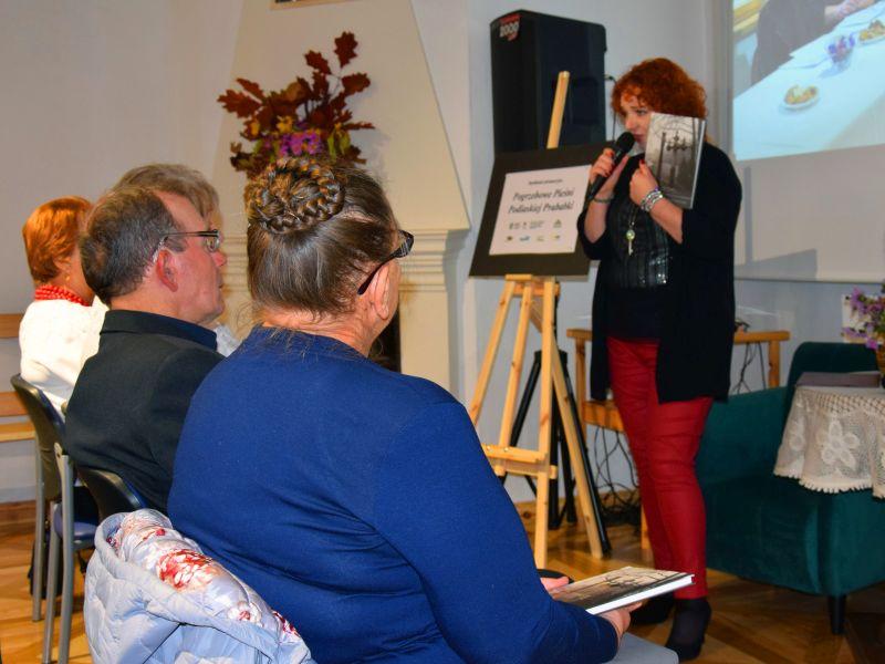 Koordynator projektu prezentuje śpiewnik. Po lewej siedzą troje trenerów warsztatów.